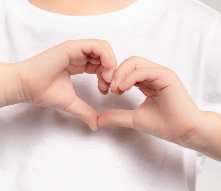 An individual using both hands to shape a heart shape sign