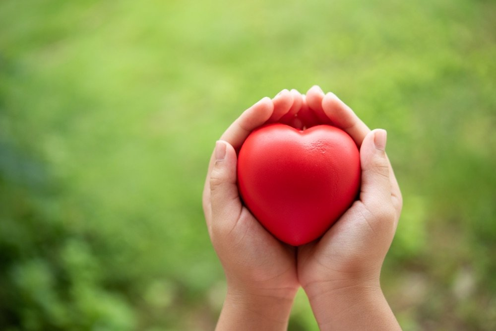 A pair of caring hands holding a heart