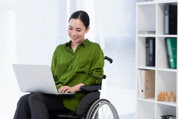 A disabled woman on a wheelchair using a laptop